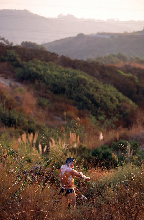 A migrant worker bathes in the hills of San Diego, California.  Cities such as San Diego, long a home for migrant field workers, are reversing their stance and forcing  migrants to leave their encampments. Please contact Todd Bigelow directly with your licensing requests. PLEASE CONTACT TODD BIGELOW DIRECTLY WITH YOUR LICENSING REQUEST. THANK YOU!
