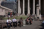 Workers rest on benches in late summer sunshine outside the Royal exchange building in the City of London.