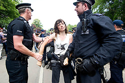 © London News Pictures. 19/08/2013. Balcombe, UK. A woman being detained by police as activists clash with police outside to the Cuadrilla drilling site in Balcombe, West Sussex on a day of of civil disobedience organised by campaign group No Dash For Gas. Cuadrilla has temporarily ceased drilling at the site, which has been earmarked for fracking, under advice from the police. Photo credit: Ben Cawthra/LNP