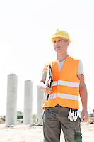 Thoughtful architect looking away while holding clipboard at construction site