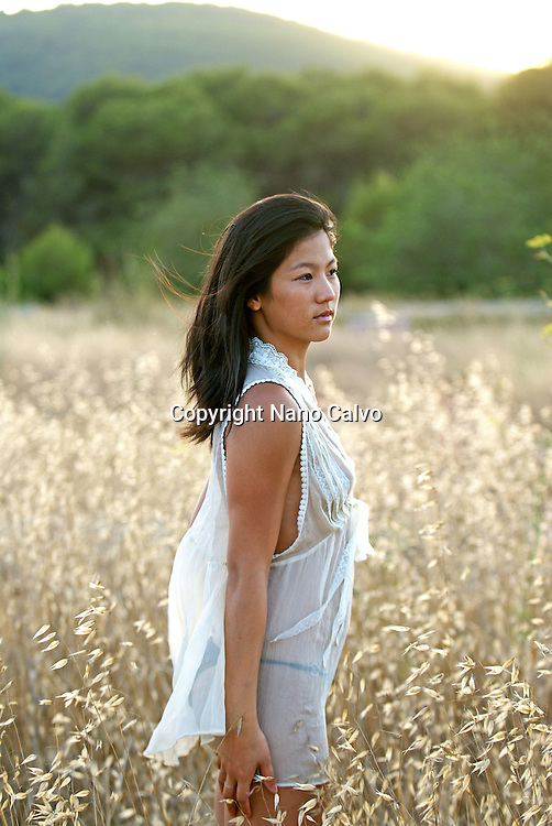 MR Portrait of a cute young asian woman in a field, at sunset