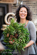 Emily Whitney, with one of hundreds of her elegant custom wreathes she hand-crafts each year for Christmas.