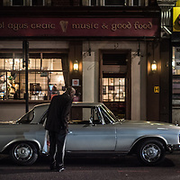 London, UK - 11 September 2014: an old man curiously looks at a parked vintage Mercedes on Kingsland High Street in Dalston, North-East London.