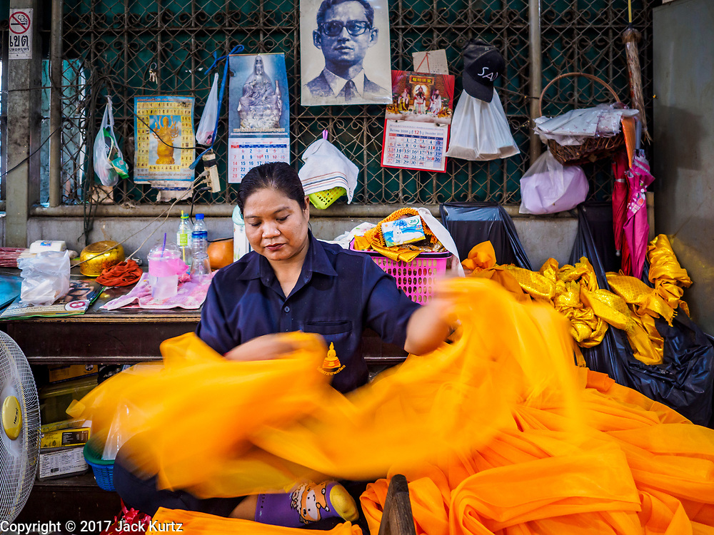 31 MAY 2017 - CHACHOENGSAO, THAILAND:  A worker rolls orange fabric used to wrap Buddha statues at Wat Sothon (also spelled Sothorn) in Chachoengsao, Thailand. The temple is one of the largest and most visited in Thailand. People make merit by paying to wrap the Buddha statues in orange robes. The temple is most famous because people leave hard boiled eggs as an offering at the temple. They ask for business success or children and leave hundreds of hard boiled eggs.     PHOTO BY JACK KURTZ