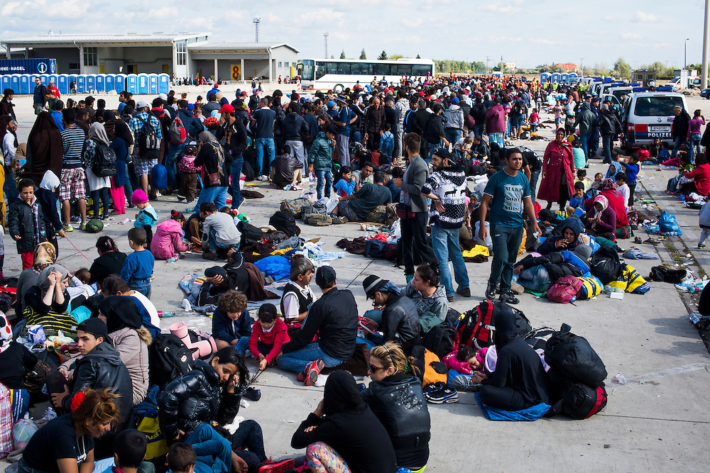 Thousands of people wait in line to catch buses and taxis to Nickelsdorf, Austria where they will board trains bound for Vienna on September 20, 2015 near Hegyeshalom, Hungary. After walking from the nearby town's train station migrants waited for hours in this transit zone parking lot.