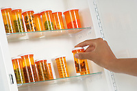 Persons hand taking pill bottle from shelf