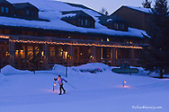 Brenda Winkler cross country skiing at dusk by Grouse Mountain Lodge in Whitefish, Montana, USA model released