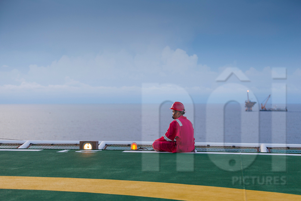 A worker sits along a helipad oil rig, offshore of Vung Tau, Vietnam, Southeast Asia