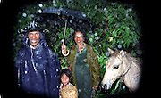 Family walking under the rain with their white horse in East Timor during rainy season. @ Martine Perret.10 Octobre 2005