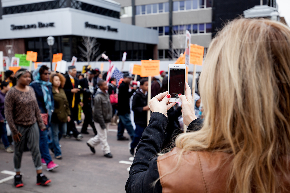 A bystander takes a photograph of demonstrators marching through the streets of Clayton, Missouri.