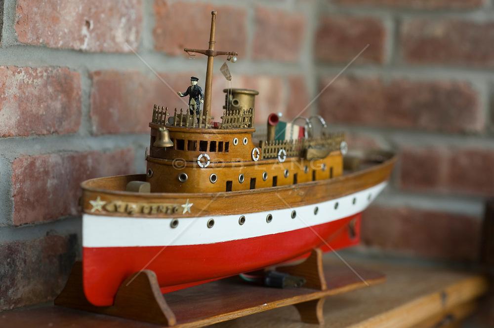 model of a ship sitting on a wooden shelf, brick background
