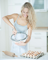 Happy woman mixing cookie batter in kitchen at counter