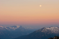 Fulll moon setting at dawn above the Coast Mountains of Britisg Columbia Canada