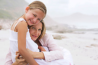 Mother and daughter (7-9) hugging on beach portrait