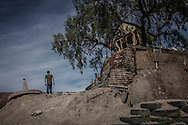 Mexican man, who asked his name not be revealed, peers over the border wall beside a treehouse built by a family living right against the US-built border wall.  Tijuana, Mexico