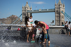 Image ©Licensed to i-Images Picture Agency. 03/07/2014. London, United Kingdom. Children play and enjoy a sunny day with the Tower Bridge in the background in one of the warmest days of the year with 28ºC in the shade. More London Riverside, City Hall area. Picture by Daniel Leal-Olivas / i-Images