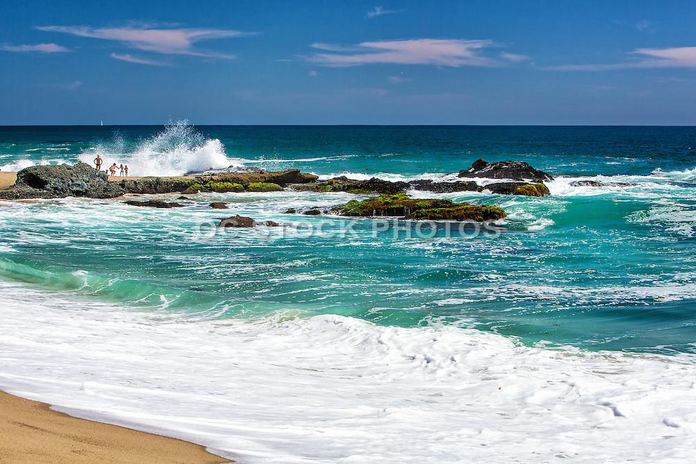 Tourists On The Beach Watching The Waves Crash In Laguna Beach