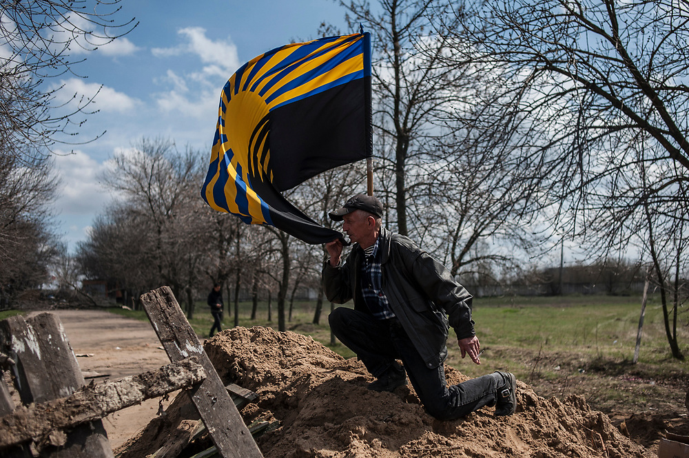 KRAMATORSK, UKRAINE - April 16, 2014: A Ukrainian man kisses the Donetsk regional flag as pro-Russia protesters gathered in front of a Ukrainian airbase in Kramatorsk, 24 hours after the army regain control of the airbase in an operation that reportedly end up with the death of four pro-Russia militia men.