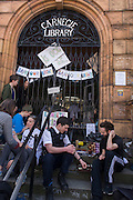 A campaigner and policeman play backgammon on the steps of the closed Carnegie Library, in Herne Hill, south London on 2nd April 2016. The angry local community in the south London borough have occupied their important resource for learning and social hub for the weekend. After a long campaign by locals, Lambeth have gone ahead and closed the library's doors for the last time because they say, cuts to their budget mean millions must be saved. A gym will replace the working library and while some of the 20,000 books on shelves will remain, no librarians will be present to administer it. London borough's budget cuts mean four of its 10 libraries will either close, move or be run by volunteers. (Photo by Richard Baker / In Pictures via Getty Images).