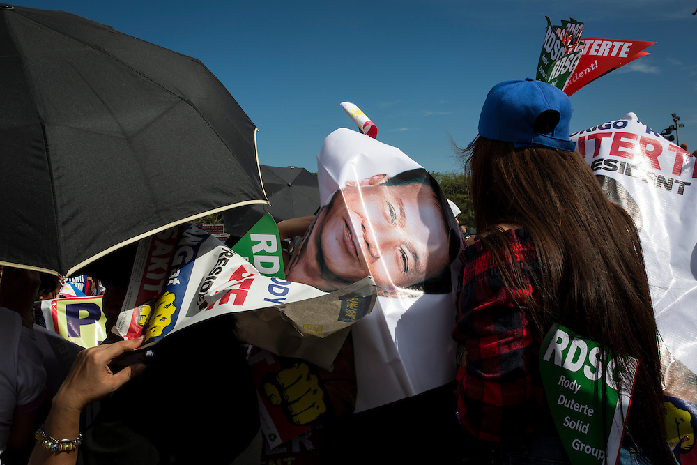 MANILA, PHILIPPINES - MAY 7: Poster of Mayor Rodrigo &quot;Digong&quot; Duterte use as a cover for heat just right before the meeting de advance of his party in Luneta Grand Stand, Manila, Philippines on Saturday, May 7, 2016. Rodrigo &quot;Digong&quot; Duterte runs for president in the 2016 Philippine national election that  will be held on May 9, 2016.<br /> <br /> Photo by Richard A. de Guzman