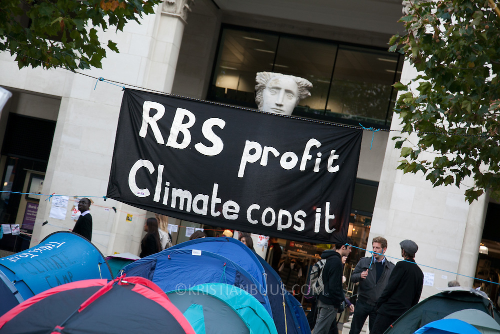 Banner hanging between trees on the edge of the camp site. Day three of the occupation - and the first Monday. The Occupy London Stock Exchange movement was formed in London in solidarity with the US based Occupy Wall Street. The movements are a respons and in anger to what is seen by many as corporate greed and a failed banking system being bailed out by the public, - which in return are suffering austerity measures to make up for the billions of lost money. The movement occupied the St Paul's Square in the City of London Sat Oct 15 after it failed to secure and occupy Pator Noster Square and the Stock Exchnage itself.