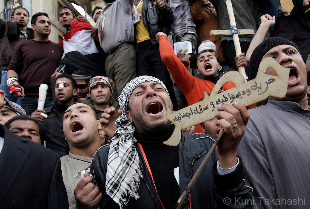 """An anti-government protester, holding a sign saying """"Freedom, Domocracy, Social Justice"""", emotionally protests at Tahrir Sq in Cairo Egypt on Feb 13, 2011 following President Hosni Mubarak's resignation. .Photo by Kuni Takahashi"""