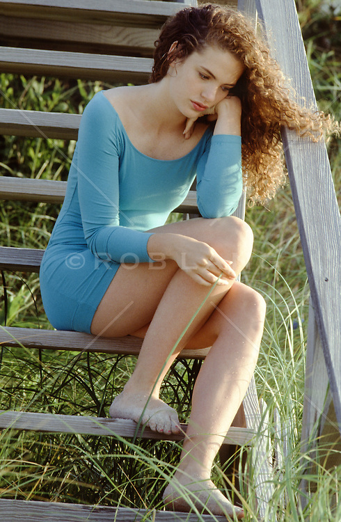 woman sitting on wooden beach steps in deep thoughts