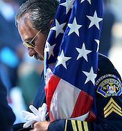 Hempstead Police Sgt. Anthony Quattropani moments before the start of a 9/11 memorial service on Denton Green across from Hempstead Village Hall to remember the victims, fallen heroes and families of the World Trade Center tragedy.  (September 11, 2013). © Audrey C. Tiernan