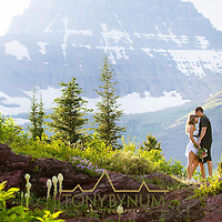 a couple stands on a rock ridge in glacier national park