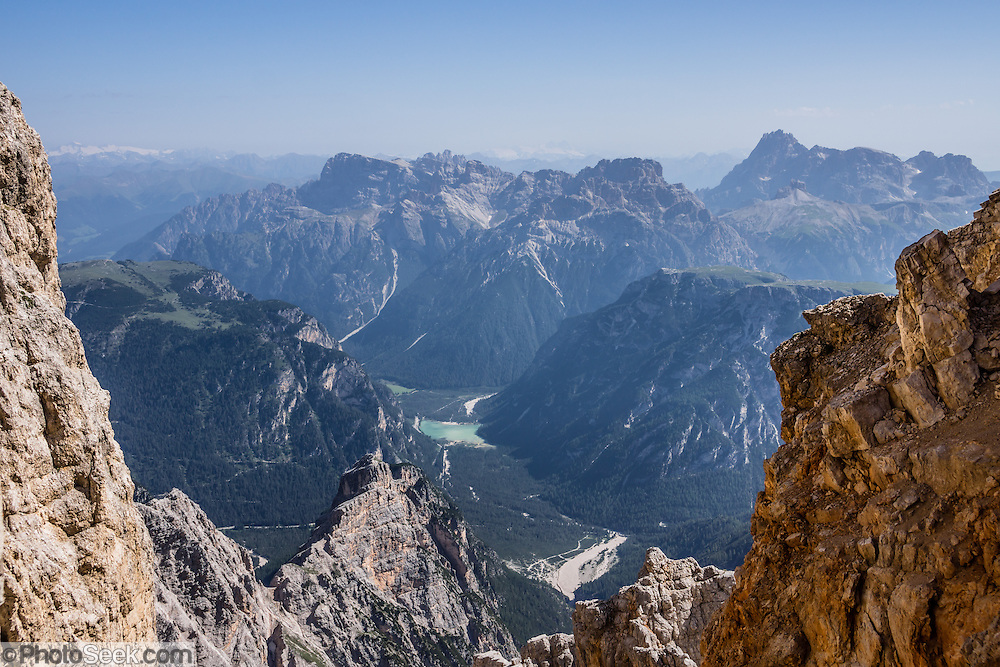 From a stairway at Rifugio Guido Lorenzi on Monte Cristallo, see Lago di Landro/Dürrensee in Val Pusteria/Pustertal beneath the Sesto Dolomites (Dolomiti di Sesto, or Sexten/Sextner/Sextener Dolomiten). A lift to Forcella Staunies on Monte Cristallo gives unforgettable views over the Dolomites mountains near Cortina d'Ampezzo, in the Province of Belluno, Veneto region, Italy, Europe. Monte Cristallo lies within Parco Naturale delle Dolomiti d'Ampezzo. Directions: From Cortina, drive 6km east on SR48 to the large parking lot for Ski Area Faloria Cristallo Mietres (just west of Passo Tre Croci Federavecchia). Take a chair-lift from Rio Gere to Son Forca (rising from 1698m to 2215m). Then take the old style ovovia (egg-shaped) Gondellift Forcella Staunies to Rifugio Guido Lorenzi (2932m) for astounding views. Climbers enjoy spectacular via ferrata routes here. The beautiful Dolomiti are part of the Southern Limestone Alps. Cortina gained worldwide fame after hosting the 1956 Winter Olympics. UNESCO honored the Dolomites as a natural World Heritage Site in 2009.