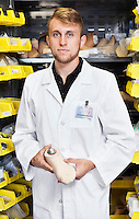 Portrait of a young technician holding artificial foot