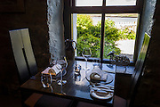 Table place setting with glassware, crockery, cutler, and napkins at renowned gastronomic five star restaurant The Three Chimneys, Isle of Skye, Scotland