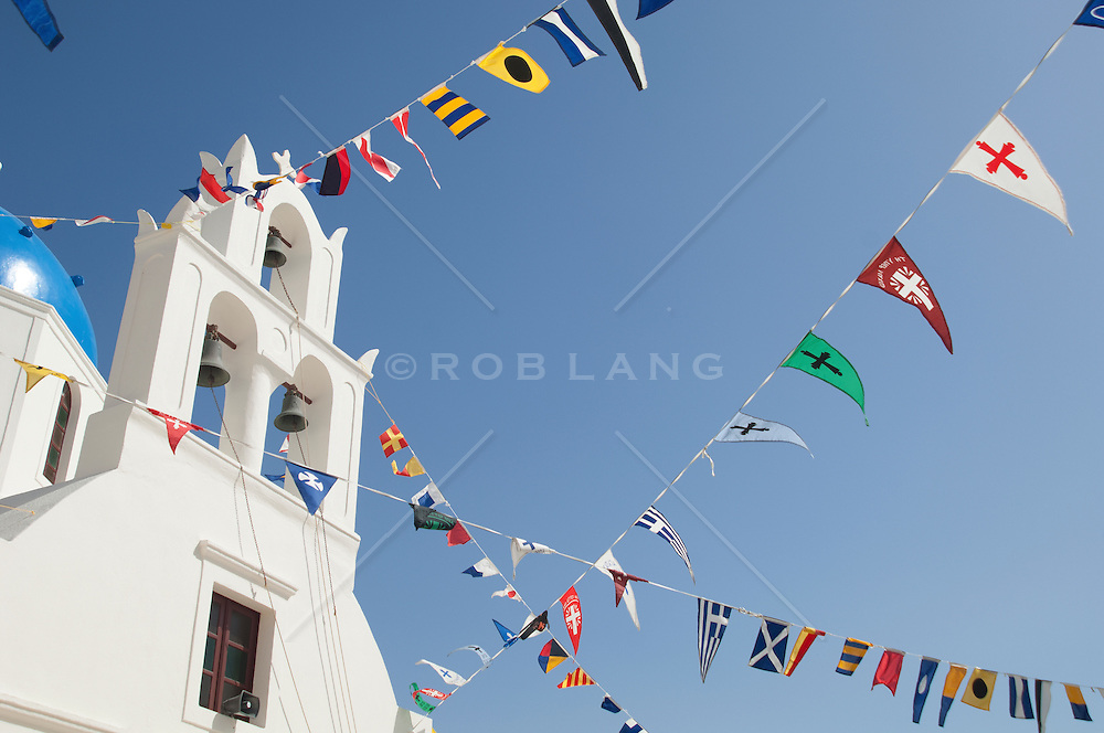 colorful flags of the world hanging from a Greek Church