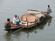 An unidentified village people sits with his family members as they shift their house to another village because floods in Chapar village, about 275 kilometers  southwest of Gauhati, capital of northeastern Indian state of Assam, Wednesday, June 30, 2004. ..Floodwaters of the Asia'a one of the largest river, Brahmaputra and its 35 tributaries have affected more than one million in all of Indian subcontinent and disrupted communication in many parts of the India and Bangladesh, sources said. (AP Photo/ Shib Shankar Chatterjee)..