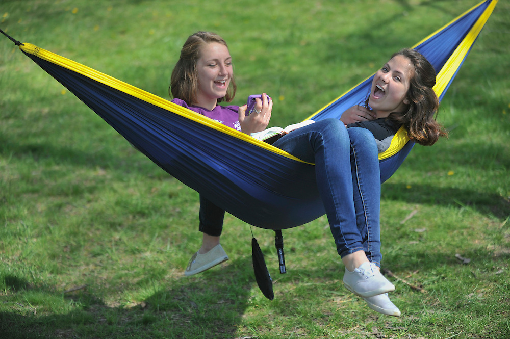 Two students hang out in a hammock on a warm spring day.