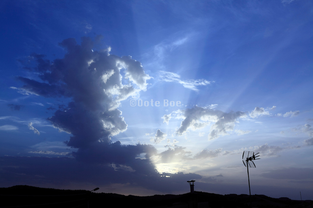 rays of sunlight with clouds and tv antenna