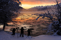 Photographers capture the sunrise on the ice-laden Chilkat River in the Alaska Chilkat Bald Eagle Preserve along the Chilkat River near Haines, Alaska. Photographers from around the world come to the Chilkat River to photograph bald eagles. During November and December several thousand bald eagles are seen along the river allowing for ample opportunities to photograph the birds along with beautiful scenery that the area offers. In 1982, the 48,000 acre area was designated as the Alaska Chilkat Bald Eagle Preserve.