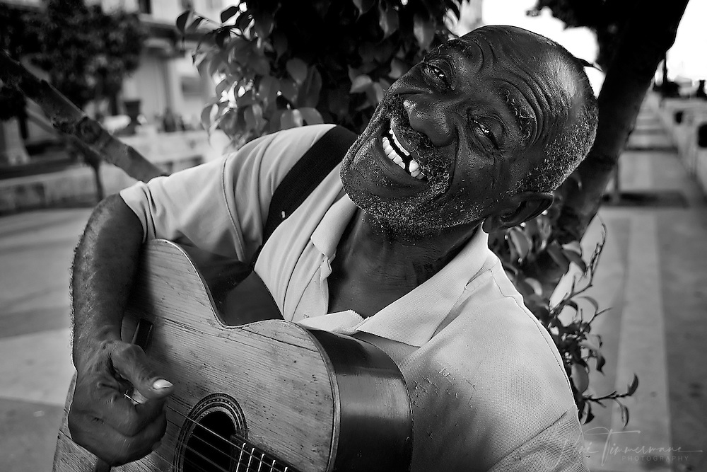 An old man with a guitar is playing songs at the Prado in Havana.