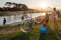 Bubbles Festival in Kuaotunu at the reserve . Adults  drink bubbles children blow bubbles. Coromandel Photographer Felicity Jean Photography
