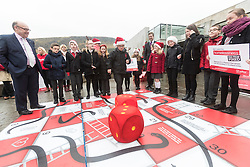 "Campaigners from Shelter Scotland raise awareness of their campaign ""Homelessness - Far From Fixed"" outside the Scottish Parliament in Edinburgh. They are joined by carol singers from Corstorphine Primary School, a Christmas tree and a giant snakes and ladders board game - Chance Not Choice - which illustrates how life chances affect people's ability to keep a roof over their head.<br /> <br /> Pictured: James Dornan (SNP) playing Chance Not Choice with Evan Jones from Costorphine Primary School throwing the dice"