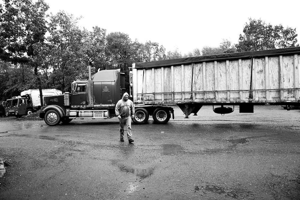 Black & White photo of Truck Driver walking away from loaded Municipal Solid Waste Transfer Truck in the rain