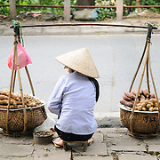 A street vendor in Hanoi, Vietnam, sell yams and other roots on the side of a road as people on scooters race by.