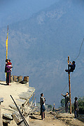 On the ledge of their house, Sangay, holding Tandin Wangchuk, watches government workers complete the electrical connections from a new small hydroelectric dam in a neighboring valley. This is the first electricity that has been brought to this region of Bhutan. Hungry Planet: What the World Eats (p. 42). The Namgay family living in the remote mountain village of Shingkhey, Bhutan, is one of the thirty families featured, with a weeks' worth of food, in the book Hungry Planet: What the World Eats.