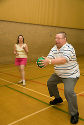 Day service user catching a ball during an indoor cricket game in the gym,