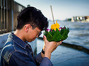 "03 NOVEMBER 2017 - BANGKOK, THAILAND: A man prays before floating a krathong in Chao Phraya River during Loi Krathong at Wat Prayurawongsawat on the Thonburi side of the Chao Phraya River. Loi Krathong is translated as ""to float (Loi) a basket (Krathong)"", and comes from the tradition of making krathong or buoyant, decorated baskets, which are then floated on a river to make merit. On the night of the full moon of the 12th lunar month (usually November), Thais launch their krathong on a river, canal or a pond, making a wish as they do so. Loi Krathong is also celebrated in other Theravada Buddhist countries like Myanmar, where it is called the Tazaungdaing Festival, and Cambodia, where it is called Bon Om Tuk.     PHOTO BY JACK KURTZ"