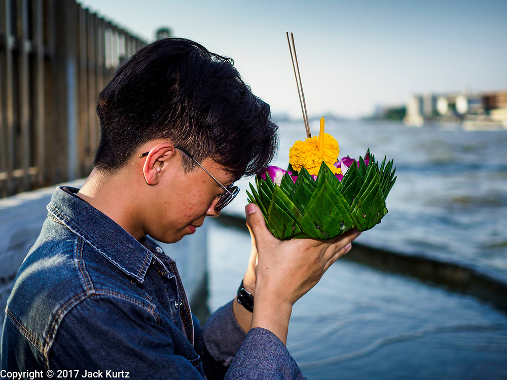 """03 NOVEMBER 2017 - BANGKOK, THAILAND: A man prays before floating a krathong in Chao Phraya River during Loi Krathong at Wat Prayurawongsawat on the Thonburi side of the Chao Phraya River. Loi Krathong is translated as """"to float (Loi) a basket (Krathong)"""", and comes from the tradition of making krathong or buoyant, decorated baskets, which are then floated on a river to make merit. On the night of the full moon of the 12th lunar month (usually November), Thais launch their krathong on a river, canal or a pond, making a wish as they do so. Loi Krathong is also celebrated in other Theravada Buddhist countries like Myanmar, where it is called the Tazaungdaing Festival, and Cambodia, where it is called Bon Om Tuk.     PHOTO BY JACK KURTZ"""