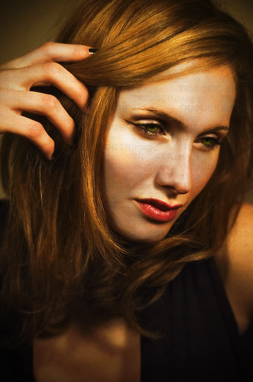 Close up of a young woman's face with hand touching hair