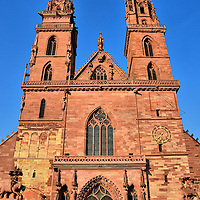 Basel M&uuml;nster Church in Basel, Switzerland <br /> If you look closely at the base of the Basel M&uuml;nster&rsquo;s left bell tower you&rsquo;ll see a patch of white sandstone mixed in among the red. That is part of the original church that was consecrated in 1019. You&rsquo;ll also see on this St. George Tower a statue of the saint dressed as a knight while slaying a dragon with his sword.  Now a Protestant church, it was rebuilt after being partially destroyed by a 1356 earthquake.  The final tower with a clock and sundial is called Martinsturm.  It was completed in 1500.