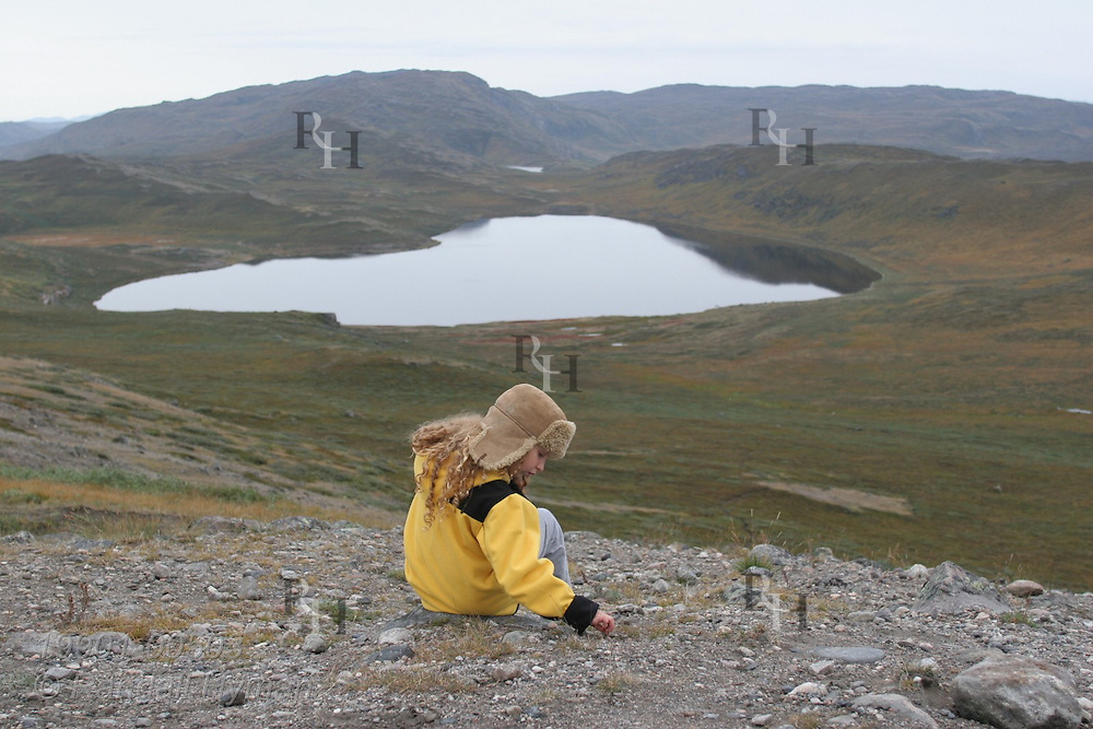 Little girl plays with stones as she sits on hillside overlooking tundra and glacial tarn in Sondre Stromfjord; Kangerlussuaq, Greenland