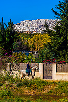 A man on horseback passes in front of the hilltop town of Salobrena, Costal Tropical, Granada Province, Andalusia, Spain.